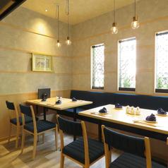 オシャレな空間にテーブルが並ぶ片側ソファーのテーブル席。