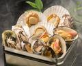 料理メニュー写真名物ガンガン焼き【牡蠣 帆立 蛤 サザエ 北寄 鮑】を缶の中に豪快に蒸し焼きにする料理。