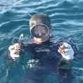 【隠岐の島・大森島付近でサザエを捕る古川さん】志な乃亭グループのサザエは隠岐の島の漁師さんに捕っていただいてます。漁は、網やモリを使うのではなく、海に潜ってひとつずつ手で捕るとてもたいへんな漁です。おかげで殻が美しく、大きいものが届きます。秋冬のイチオシ食材、ぜひ食べてください!(10月~2月)