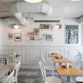 【1F】白を基調とした落ち着いた雰囲気の店内に並んだテーブル席は2名様~ご案内可能です。華やかなデザートやコーヒーなどのカフェメニューもございますので渋谷でカフェをお探しならEMANONへ♪