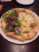 イタリアンレストラン めぐるの生ハムとルッコラのピザの写真